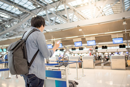young asian check in online by using smartphone and waiting for drop his luggage at airline check-in counter inside the international airport terminal, travel lifestyle concept