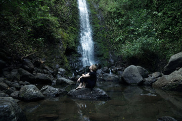 woman sitting in front of waterfall