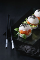 Mini rice sushi burgers with smoked salmon, green salad and sauces, black sesame served on black square plate with chopsticks and textile napkin over black background. Modern healthy food