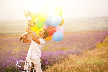 Father and son playing with balloons on lavender field