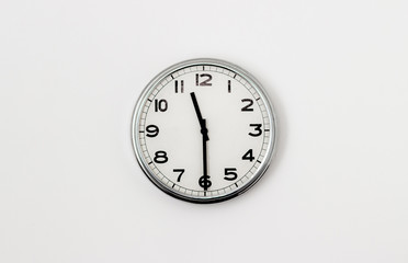 White Clock hanging on a white wall showing time 11:30