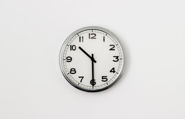 White Clock hanging on a white wall showing time 10:30