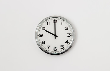 White Clock hanging on a white wall showing time 10:00