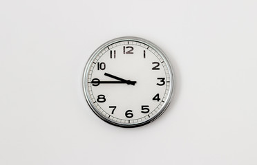 White Clock hanging on a white wall showing time 9:45