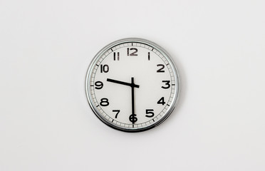 White Clock hanging on a white wall showing time 9:30