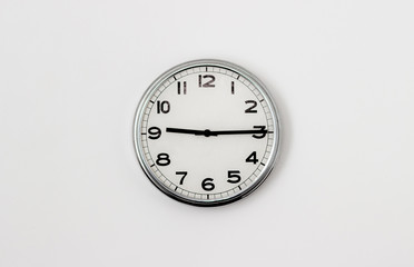 White Clock hanging on a white wall showing time 9:15