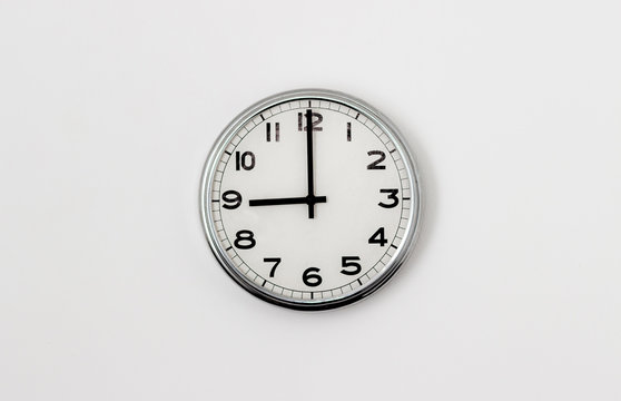 White Clock hanging on a white wall showing time 9:00