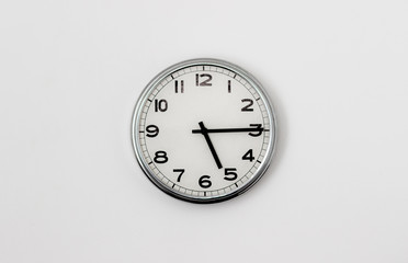 White Clock hanging on a white wall showing time 5:15