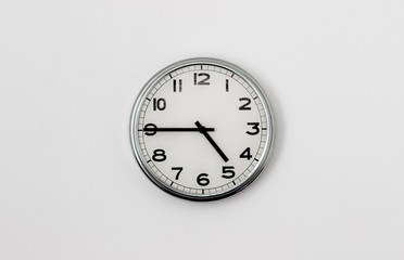 White Clock hanging on a white wall showing time 4:45