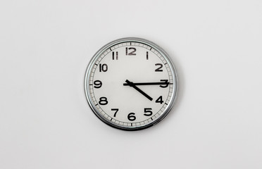 White Clock hanging on a white wall showing time 4:15