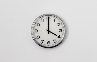 White Clock hanging on a white wall showing time 4:00