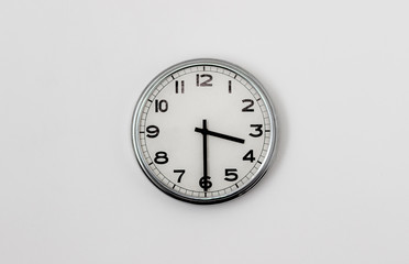 White Clock hanging on a white wall showing time 3:30