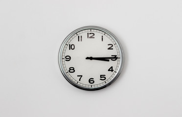 White Clock hanging on a white wall showing time 3:15