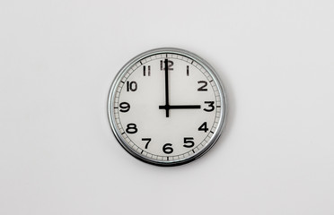 White Clock hanging on a white wall showing time 3:00