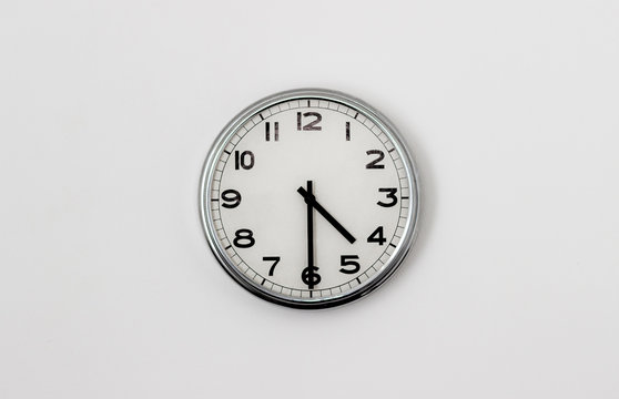 White Clock hanging on a white wall showing time 4:30