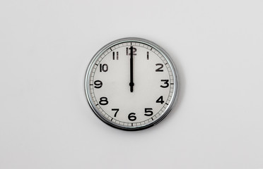 White Clock hanging on a white wall showing time 12:00
