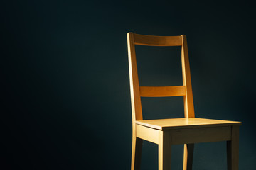 Empty wooden chair in dark room