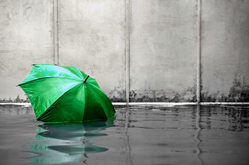 Green umbrella floating concept. Flooded on street. .Waiting for help me after the rain. Black and white colors. Close up.
