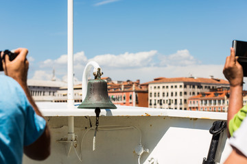 tourists taking pictures on a boat going to Venice; a bell is hanging on a boat's bow; view of a city from water
