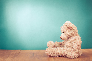 Teddy Bear retro old toy siting alone front mint green background. Vintage style filtered photo