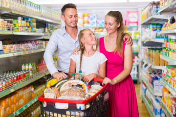 Charming woman and man with teenager girl in the shop
