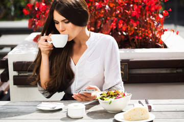 Brunette woman with long hair drinks coffee at the table