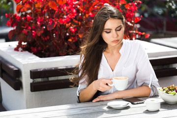 Woman holds a cup of coffee sitting at the table outside
