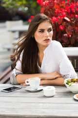 Girl with long hair drinks coffee sitting in the restaurant