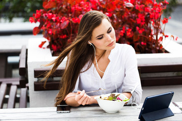 Brunette woman watches something on her tablet while sitting in the restaurant