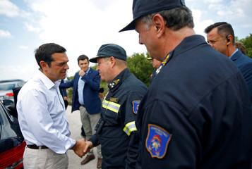 Greek PM Tsipras meets with firefighters as a wildfire is being contained after four days near the village of Kapandriti, north of Athens
