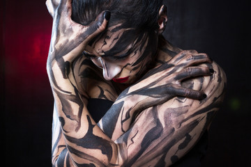The painted woman with black paint tightly closes her hands and digs her fingers into the skin.