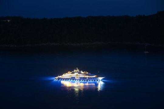 An illuminated luxury yacht in the Adriatiac sea at night in Dalmatia, Croatia.