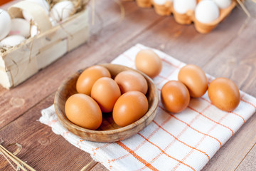 Close-up view of raw chicken eggs on wooden background