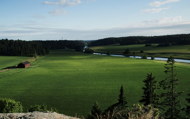 Finnish countryside, river running through, green vegetation and a barn