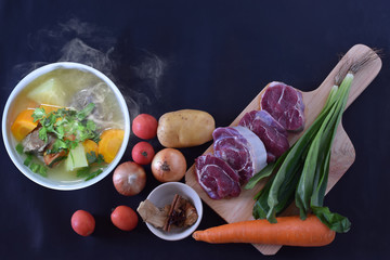 Beef soup in white bowl with raw ingredients.
