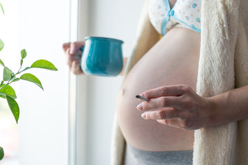 A pregnant woman with a big belly holding a coffee and a cigarette. Concept of Smoking and bad habits during pregnancy