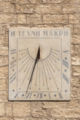 Old sundial in a stone facade