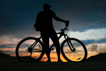 Silhouette of cyclist on the background of sunset. Biker with bicycle on the sand during sunrise
