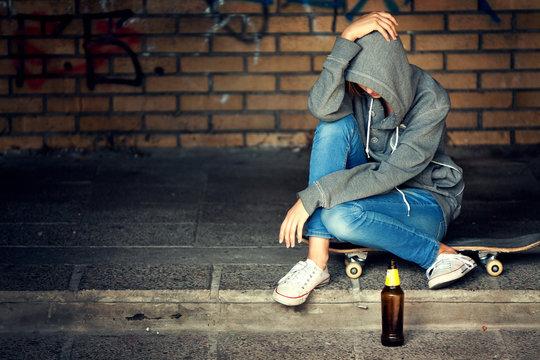 Despair Teenager Girl Sitting with Beer in Dark Doorway