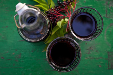 Glasses of fresh elderberry syrup and elderberries on a wooden table, top view