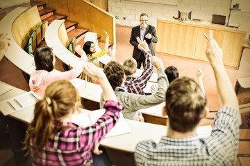 Students raising hands with teacher in lecture hall