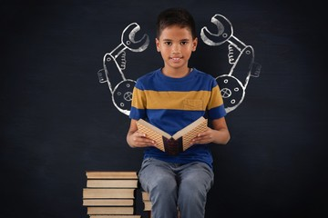 Composite image of schoolboy sitting on stack of books