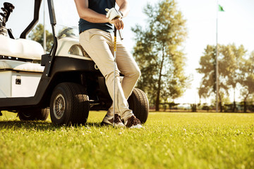 Cropped image of a male golfer leaning on a golf cart