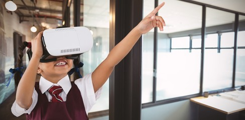 Composite image of school girl pointing while using vr headset