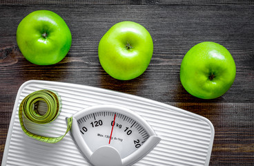 Lose weight concept. Bathroom scale, measuring tape, apples on wooden background top view