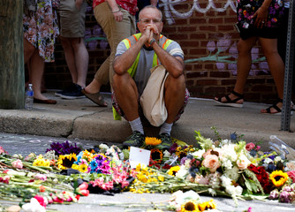 A man looks at flowers placed on the road where Heather Heyer was killed when a suspected white nationalist crashed his car into anti-racist demonstrators in Charlottesville, Virginia