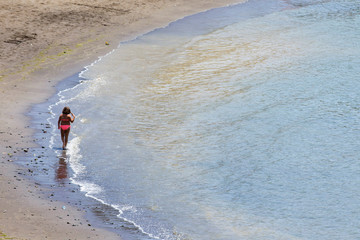 """A girl walk at """"Las Maranuelas"""" beach, one of the beaches where people have been warned about a micro algae invasion which can produce some health problems, in Mogan"""