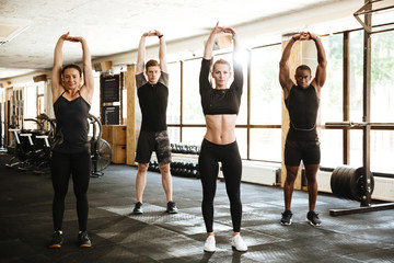 Group of young fit people doing sport exercises together
