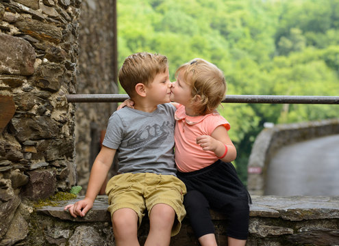 lovely adorable brother and sister giving each other a kiss for family love
