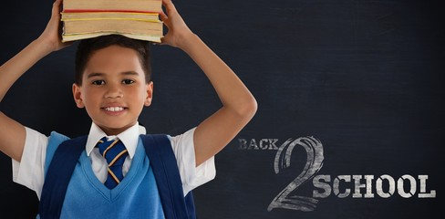 Composite image of smiling schoolboy carrying books on head over